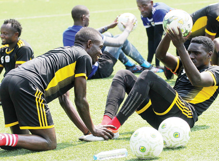 Cranes striker Emma Okwi (L) and defender Timothy Awany during a training session on Monday
