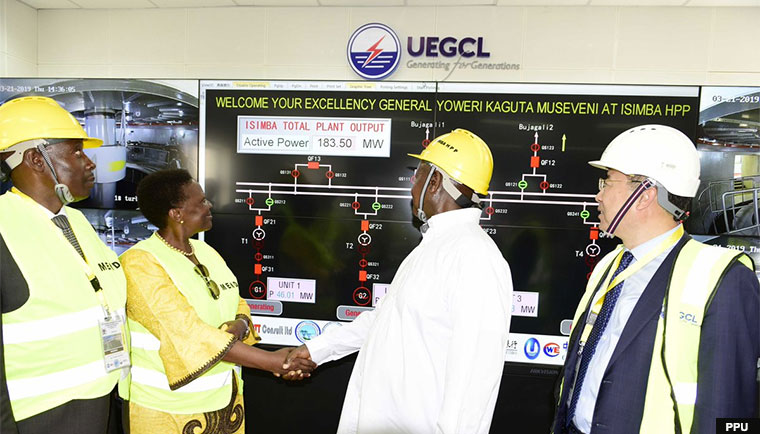 Museveni shakes hands with Energy minister Irene Muloni after commissioning the Isimba power plant