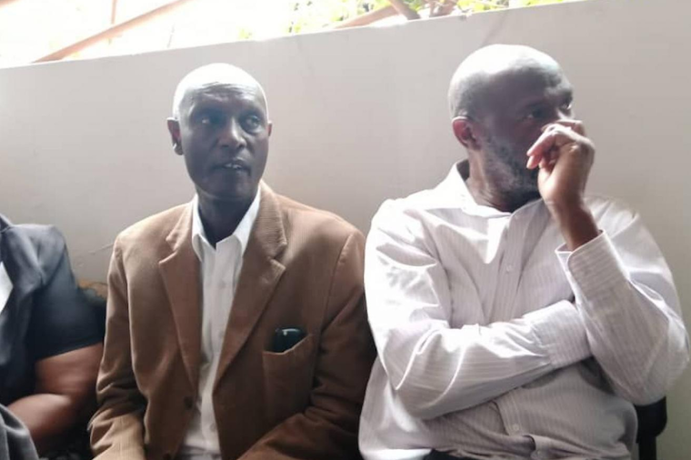 John Muhanguzi Kashaka (L) and Henry Bamutura waiting to be taken to prison