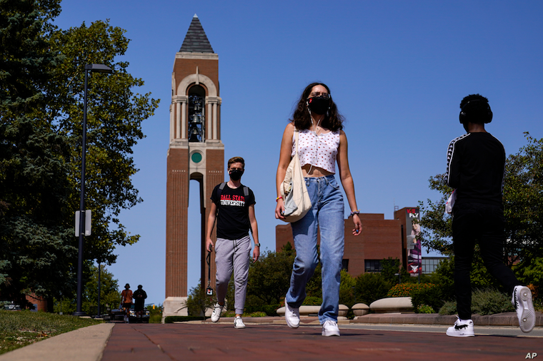 Masked students walk through the campus of Ball State University in Muncie, Indiana