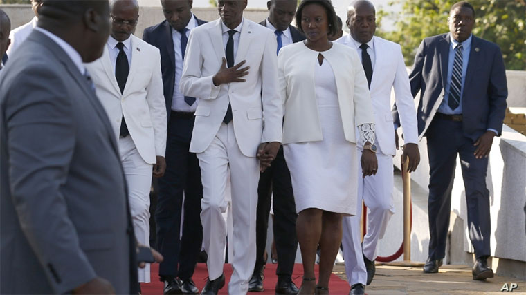 Accompanied by First Lady Martine Moïse, center right, and and acting prime minister Jean Michel Lapin, center left, President Jovenel Moise, center, arrives to lay flowers to mark the anniversary of the death of Haitian revolution leader