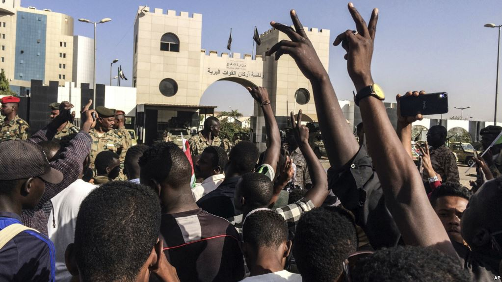 Sudanese demonstrators march with national flags as they gather during a rally demanding a civilian body to lead the transition to democracy, outside the army headquarters in the Sudanese capital Khartoum