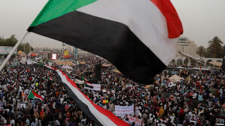 Thousands of protesters wave Sudanese flags, hold banners and chant slogans during a demonstration in front of the Defense Ministry in Khartoum, Sudan
