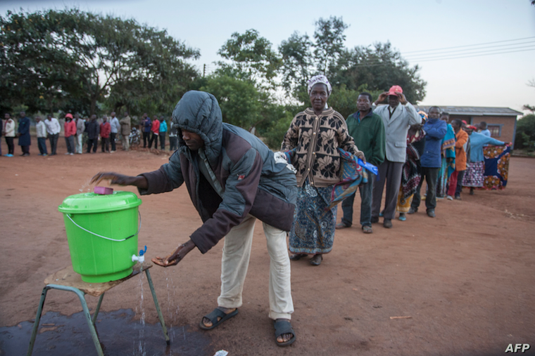 Residents of Lilongwe, Malawi queue to wash hands during the elections