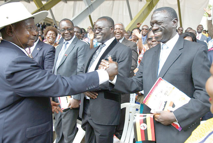 President Yoweri Museveni (L) shakes hands with Kizza Besigye
