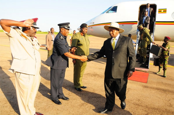Museveni shakes hands with police boss Martins Okoth Ochola