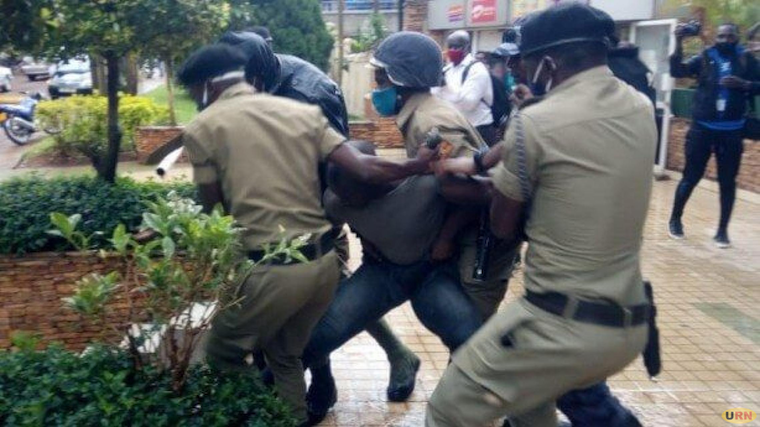 Police officers arresting NUP supporters