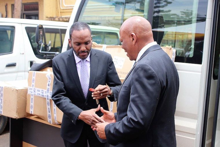 IOM Chief of Mission Ali Abdi (left) hands over the bus keys to DCIC boss Maj Gen Apollo Kasiita-Gowa
