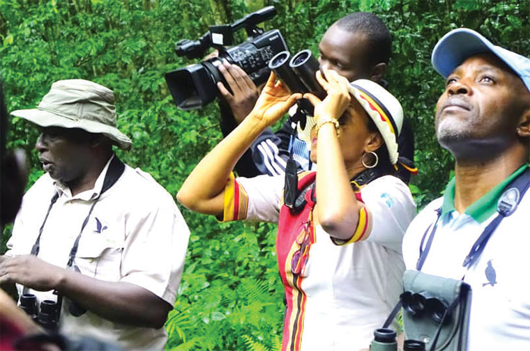 Ajarova (with binoculars) and Achillies Byaruhanga birding in Mabira forest